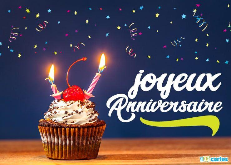cupcake au topping blanc décoré d'une cerise et de bougies d'anniversaire