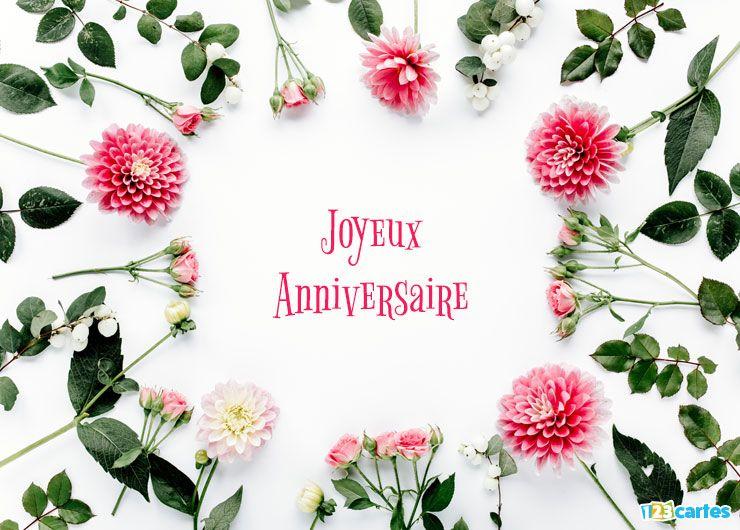 fleurs disposées en forme de cercle avec au milieu le texte joyeux anniversaire