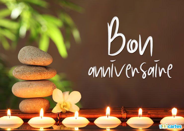 décor zen avec des bougies qui flottent sur l'eau, une fleur de Frangipani et des pierres de basalte assemblées verticalement