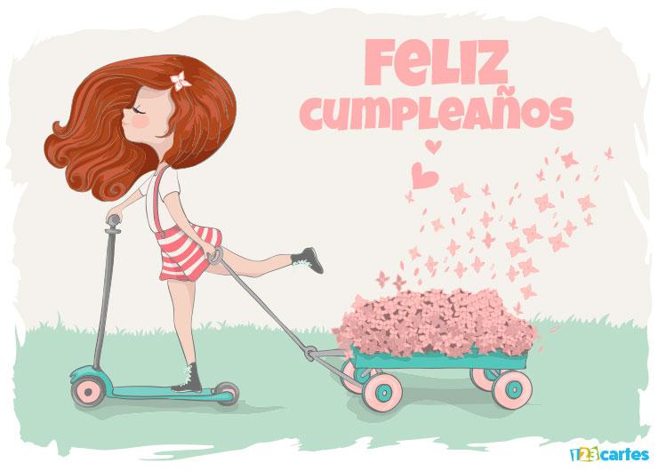 élégante fille sur une trottinette qui tire un petit chariot rempli de roses avec joyeux anniversaire en Espagnol